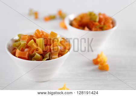 Hearts uncooked pasta in bowls on wooden table closeup