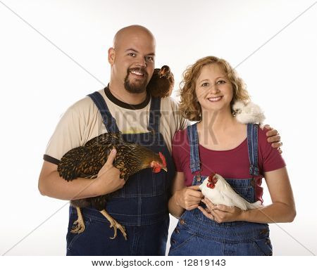 Caucasian mid-adult woman and man with chickens.