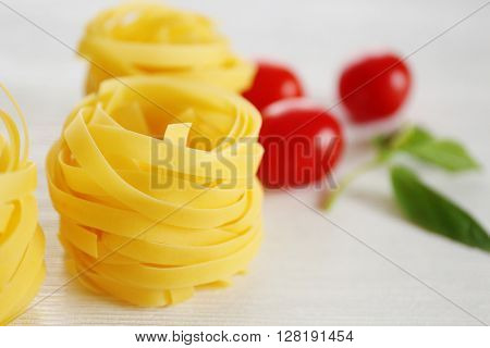 Fresh uncooked pasta with cherry tomatoes and green leaves on wooden table closeup