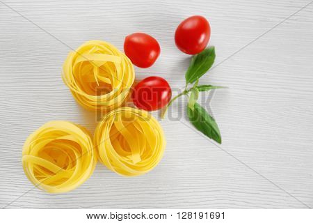 Fresh uncooked pasta with cherry tomatoes and green leaves on wooden table, top view