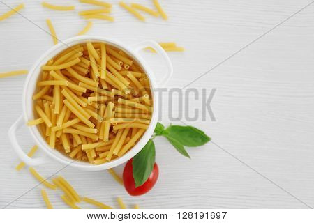 Fresh uncooked pasta in bowl on wooden table, top view