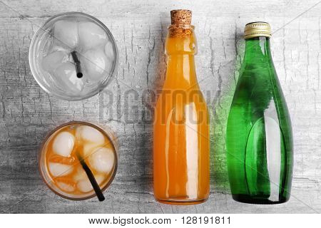 Fresh cocktails with soda bottles on grey table background, top view