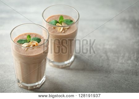 Two glasses of fresh banana cocktail  with peanuts on grey background