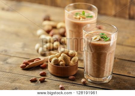 Fresh banana cocktail with peanuts on wooden table