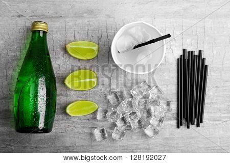 Fresh cocktail preparation: soda bottle, ice cubes, slices of lime  on grey table background, top view