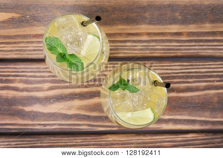Glass of lemon soda with fresh mint on wooden background