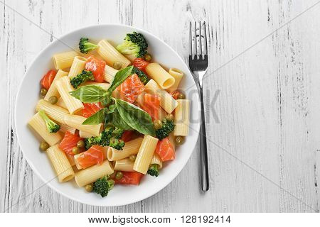 Plate of pasta with salmon and broccoli on wooden table, top view