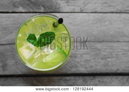 Glass of lemon soda with fresh mint on rustic wooden background
