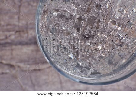 Glass of soda with ice on rustic wooden background