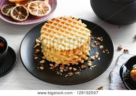 Fresh waffles with honey and dried oranges on wooden background