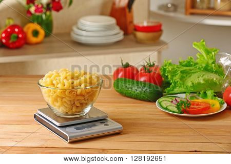 Bowl of dry pasta and digital kitchen scales on wooden table