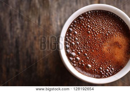 Cup of hot coffee on rustic wooden background, close up