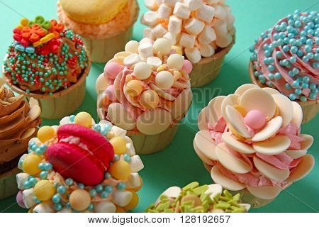 Tasty cupcakes with original decoration on turquoise background