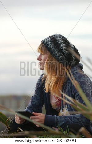 Woman reading outdoors, staring at the distance