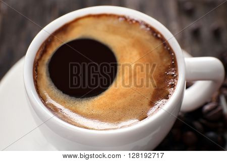 Cup of hot coffee with roasted beans, close up