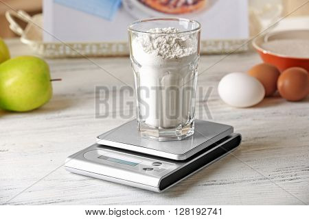 Glass of flour and digital kitchen scales on light wooden table