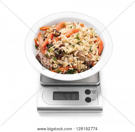 Bowl with pilaf on digital kitchen scales, isolated on white