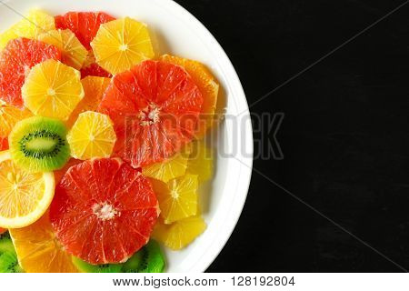 Plate of fresh peeled and sliced citrus on dark wooden background