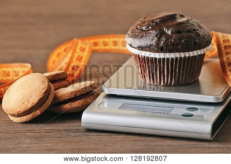 Chocolate cupcake with centimeter and digital kitchen scales on wooden table