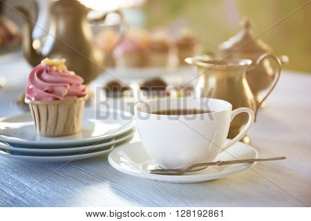 Cupcake with pink cream and cup of tea on wooden table indoors