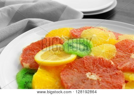 Plate of fresh peeled and sliced citrus, closeup