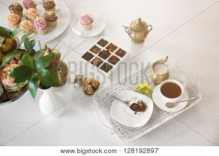 Delicious tea and cakes on wooden background