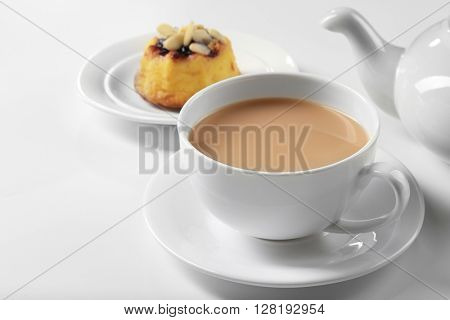 Milk tea with tea pot and a dessert on white background