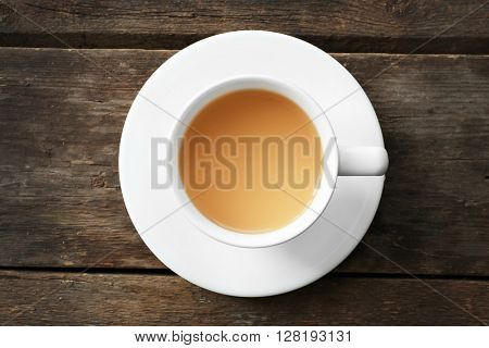Cup of tea with milk on wooden background, top view