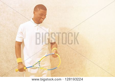 Squash player with racquet isolated on white background. Happy black man smiling and looking down on squash court.