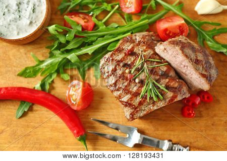 Delicious grilled steak on cutting board, closeup