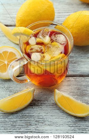 Glass of ice lemon tea on wooden table