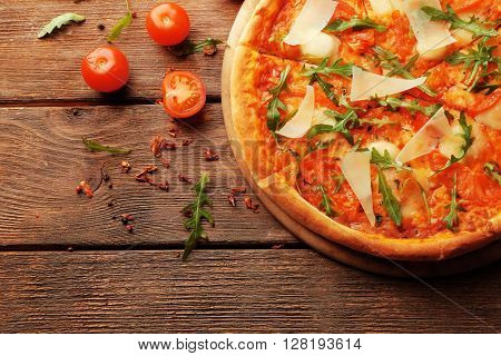 Margherita pizza with tomatoes, Parmesan and arugula on wooden background