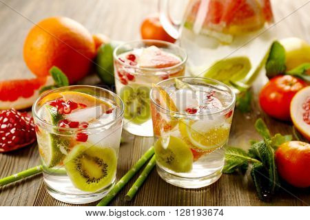 Refreshing cocktails with ice, pomegranate seeds and slices of fruits on wooden background