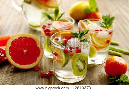 Refreshing cocktails with ice, mint, pomegranate seeds and slices of fruits on wooden background
