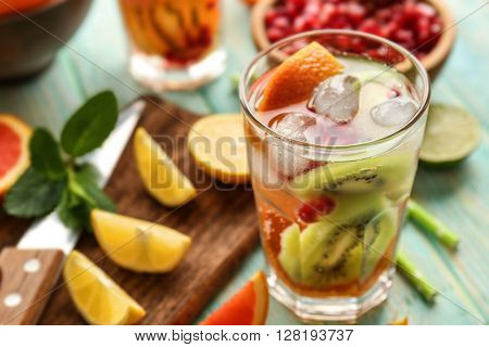 Refreshing cocktail with ice, mint, pomegranate seeds and slices of fruits on blue wooden background