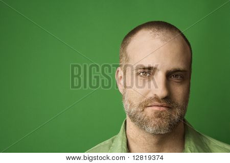 Head shot of Caucasian man with beard and receding hairline against green background.