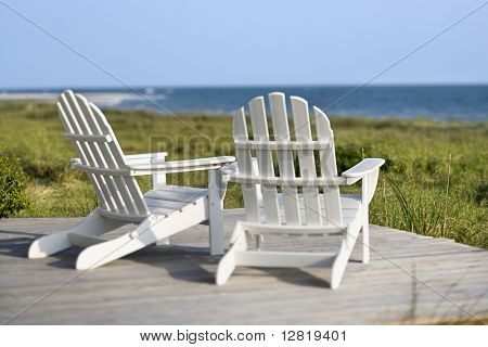 Adirondack chairs on deck looking towards beach on Bald Head Island, North Carolina.