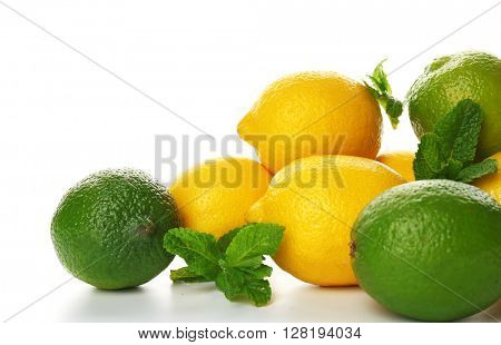 A heap of lemons and limes with mint sprigs isolated on a white background, close up