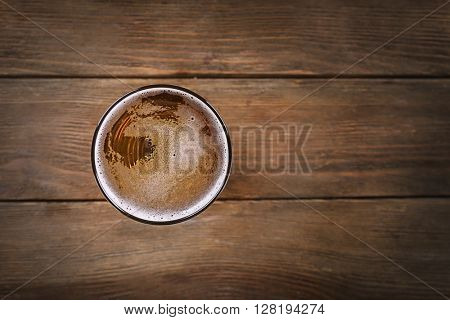 Glass of light beer on wooden background