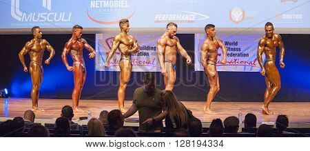 MAASTRICHT THE NETHERLANDS - OCTOBER 25 2015: Male bodybuilders Ali Rezah from Iran with other competitors flex their muscles and show their best physique in a side pose on stage at the World Grandprix Bodybuilding and Fitness of the WBBF-WFF