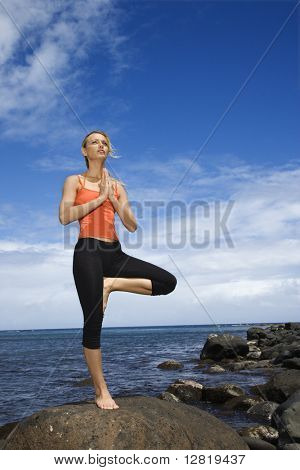 Caucasian young adult woman doing yoga on rocky shore.