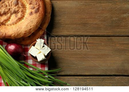 Fresh fried bread with other products on wooden table closeup
