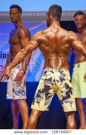 MAASTRICHT THE NETHERLANDS - OCTOBER 25 2015: Male physique model shows his best back pose at championship on stage at the World Grandprix Bodybuilding and Fitness of the WBBF-WFF on October 25 2015 at the MECC Theatre in Maastricht the Netherlands
