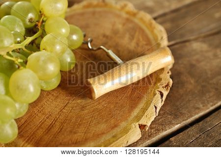 Tailspin with bunch of grapes on wooden background
