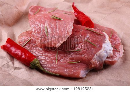 Row beef steak with red chili on paper background