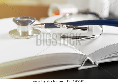 Stethoscope with open book on wooden background. Medical literature concept