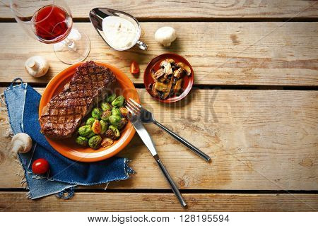 Grilled steak with vegetables on wooden table