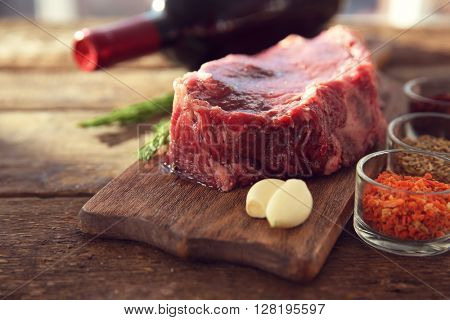 Raw pork steak with bottle of red wine and spices on wooden background