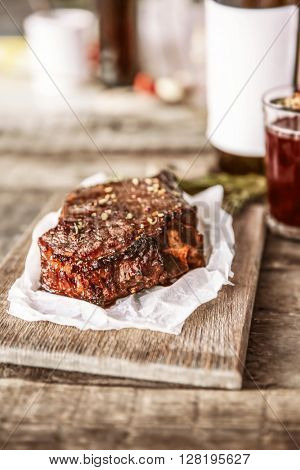 Roasted pork steak with wineglass  and spices on wooden background