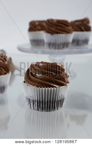 Chocolate cupcake on light glass background, close up